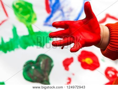 Child hand with red color on paintings background