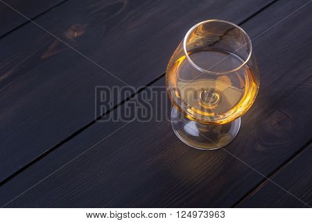 Snifter glass with brandy on dark wooden surface