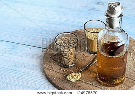 Mustard seeds, mustard powder and mustard oil in glassware on a wooden board
