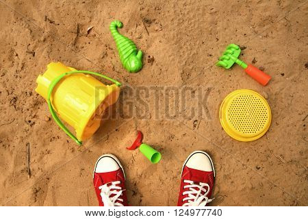 Playing in a sandbox. Red sneakers and sand toys: bucket, shovel, rake, sieve and seahorse.
