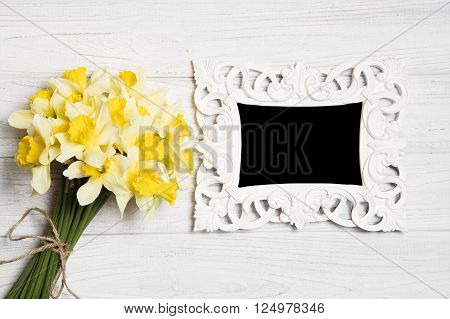 Daffodil bouquets and picture frame on white wooden background.