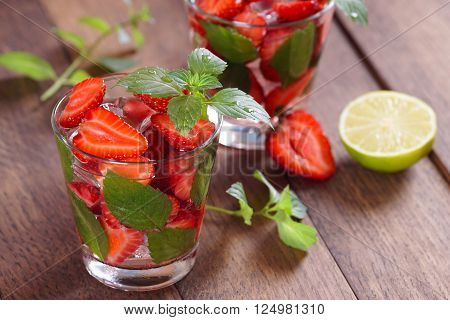 Strawberry mojito at the bar. Mojito on a brown background.