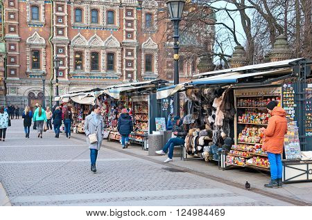SAINT - PETERSBURG, RUSSIA - APRIL 8, 2016: People near open air souvenir shops next to The Church of the Resurrection (Savior on the Spilled Blood) and Mikhaylovskiy Garden