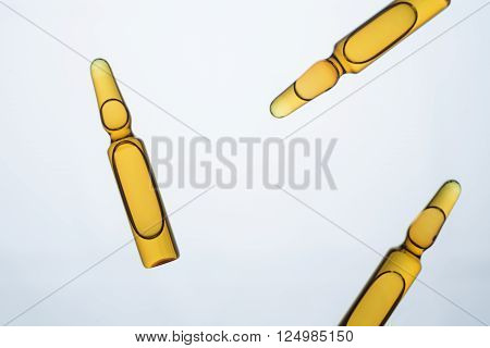 Three amber-colored ampoules isolated on light background