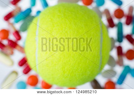 Tennis ball many coloured pills of different size at background. Concept of medicine. Mock up.