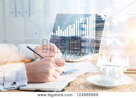 Businessman drawing business graphs in copybook at desk. Double exposure