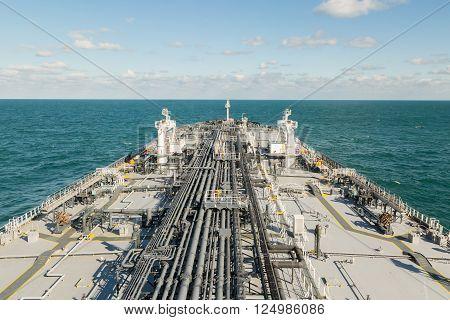 Oil tanker is proceeding in blue ocean under cloudy sky - stock photo.