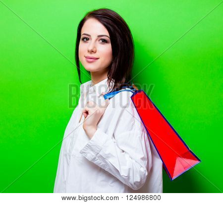 portrait of the beautiful young woman with red shopping bag on the green background