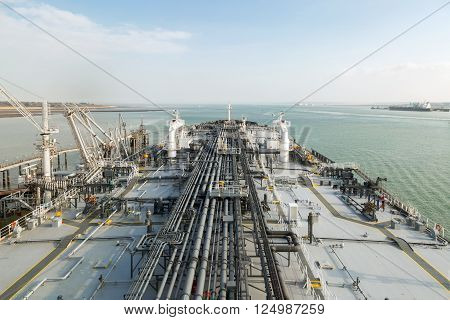 Oil product tanker during cargo operation moored to the jetty with connected cargo line to the terminal.