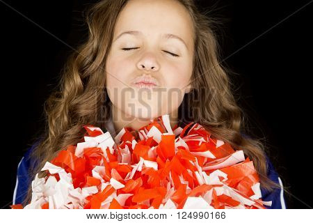 cute high school cheerleader portrait puckering, kissing into camera with her eyes closed