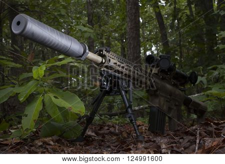 Modern sporting rifle with a silencer in a bunch of trees