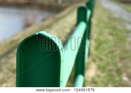 Green railing with blurred background - river and path on sunny day