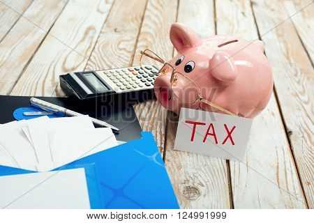Pig moneybox and calculating equipment on wood background