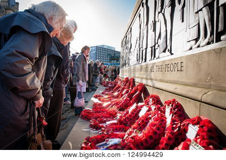 LIVERPOOL, UK: November 9th 2015: People pay their respects by laying poppy wreaths at the remembrance monument outside St Georges Hall in Liverpool