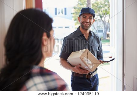 Woman Receiving Package From Courier At Home