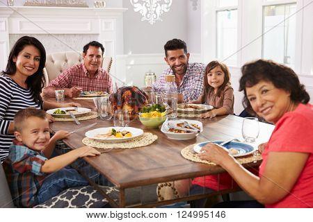 Extended Hispanic Family Enjoying Meal At Table
