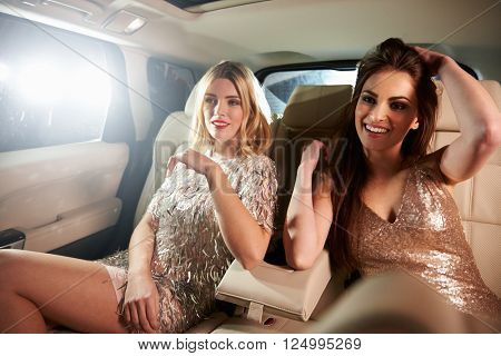 Two glamorous women relax in the back of a limo, in-car view