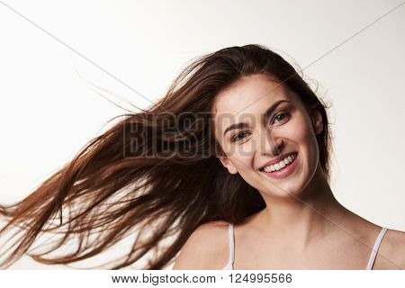 Dark haired, late teen girl, hair blowing, smiles to camera