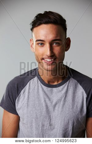 Vertical waist up studio portrait of smiling young man