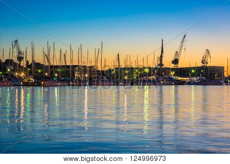 Shipyard in small coastline town Trogir in summer dawn, waterfront view. Silhouette of shipyard, Croatia.