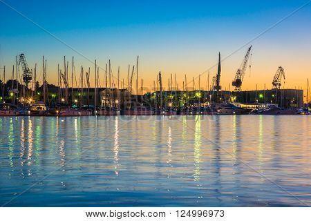 Shipyard in small coastline town Trogir in summer dawn, waterfront view. Silhouette of shipyard, Croatia.