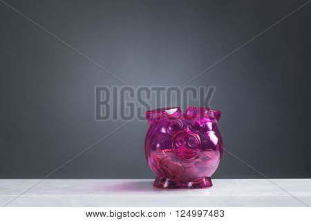 A pink Piggybank with flowers in front of grey background. A hand is feeding the bank with a 5 euro note.