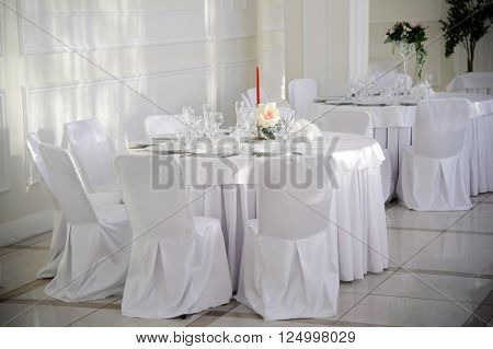 Table with chairs covered and white tablecloth with the dishes. Banquet table for guests. Served luxurious food table at the party.  Interior of the Banquet hall in the restaurant, in white.