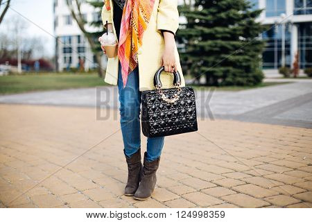close-up portrait of a fashionable young lady posing in the city, accessories, spring shoes, perfect feet, the spring collection of boots, stylish gray ankle boots, fashionable yellow coat, black bag, coffee.