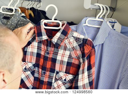 closeup of a young caucasian man picking a plaid shirt from the closet