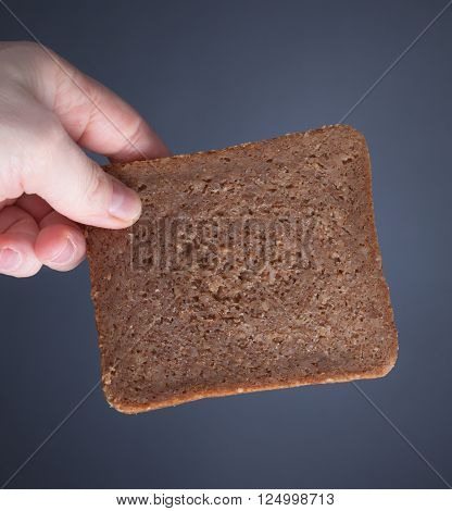 A hand holds a slice of whole weat bread in front of grey background.