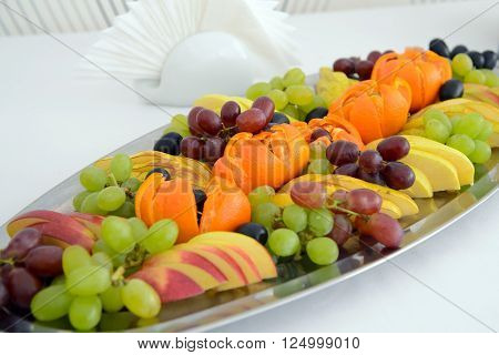 Vegetarian food. A dish with mixed fruit on the holiday table. Bananas and apples, grapes and oranges on a platter. Healthy food for dessert.
