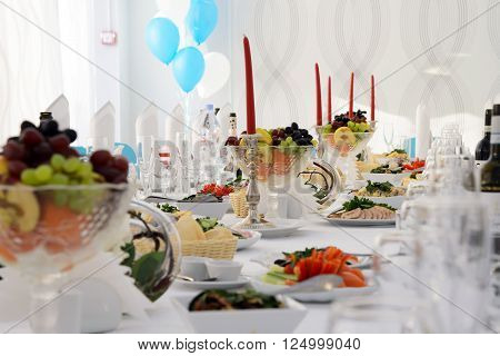 Banquet table with Cutlery and tableware, festive table with food for a celebration. Table with white tablecloth served to guests. The table in the restaurant. Luxury Desk for the celebration.