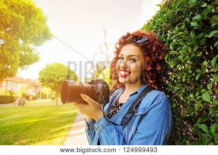 Outdoors portrait of fashionable young curly redhead female photographer holding digital camera, smiling, standing in park on sunny spring day, wearing denim shirt. Horizontal, vibrant, retouched.