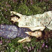 Zwei romantische Mädchen auf Blumenwiese liegend