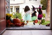 Three Children In Halloween Costumes Trick Or Treating poster
