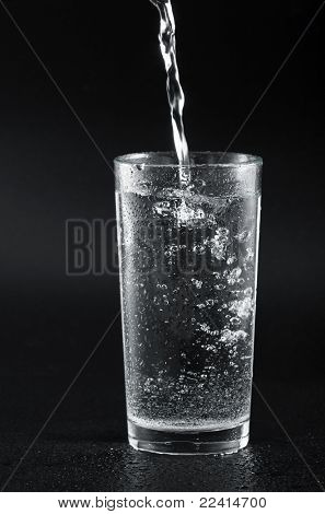 water being poured into a glass against black  background