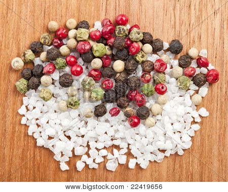 mixed pepper with salt crystal on a wooden surface