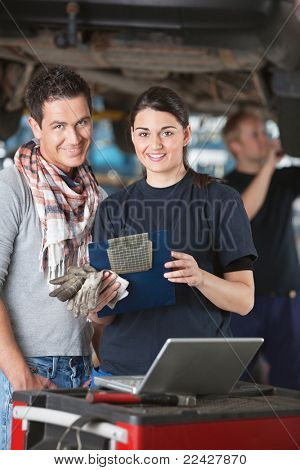 Portrait of female mechanic worker standing with customer