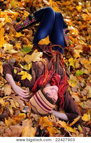 Smiling happy girl lying in autumn leaves. Outdoor.