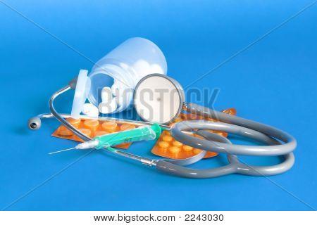 Stethoscope, Pills And Syringe On Blue Background