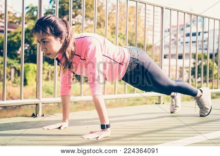 poster of Fitness sport girl fashion sportswear doing yoga fitness exercise in street. Fit young asian woman doing training workout in morning. Young happy asian woman stretching at park after running workout.