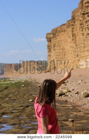 Young Girl Pointing At Dramatic Coastline