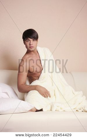 Young sexy man sitting on a bed.