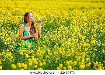 woman start soap bubbles on yellow flower field