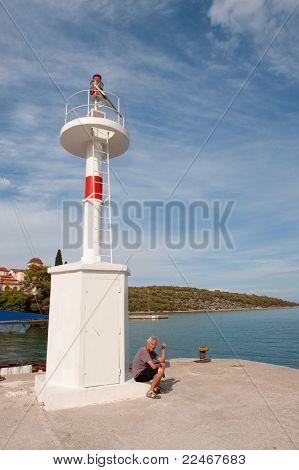 Hombre sentado cerca de Faro de luz en Griego Puerto Nea Epidauro