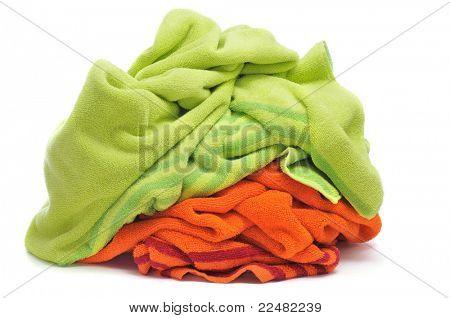 un par de toallas de playa, una verde y una naranja, sobre un fondo blanco