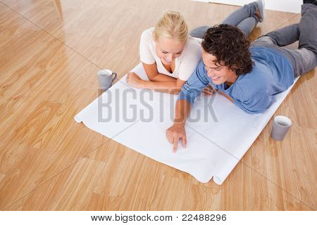 Young Man Showing A Point On A Plan To His Fiance