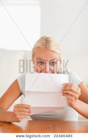 Woman Looking At A Letter In Disbelief