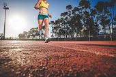 Female Fitness Model And Track Athlete Sprinting On An Athletics Track Made From Tartan poster