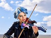 Playing viola woman perform music on violin in park outdoor. Girl with blue hairstyle and eyebrows p poster
